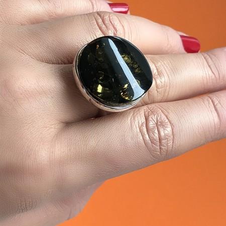 Pierścionek z dużym zielonym bursztynem wykonany ze srebra 925 w prostej oprawie.