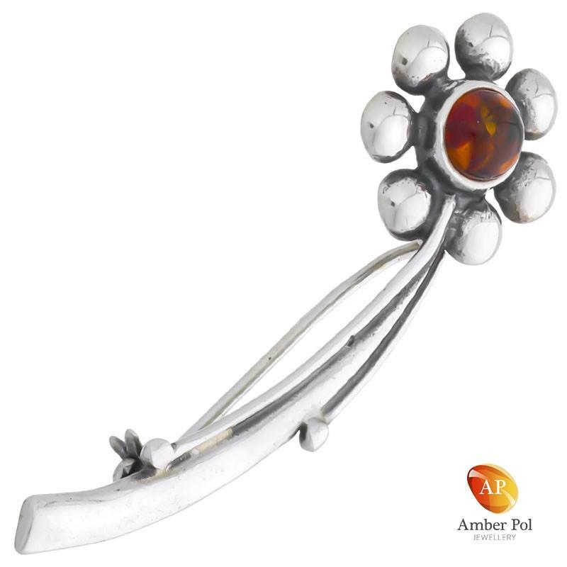 Broszka srebrna 925 z bursztynem w kolorze koniaku jako środek kwiatka otoczona srebrnymi listkami, na łodyżce.