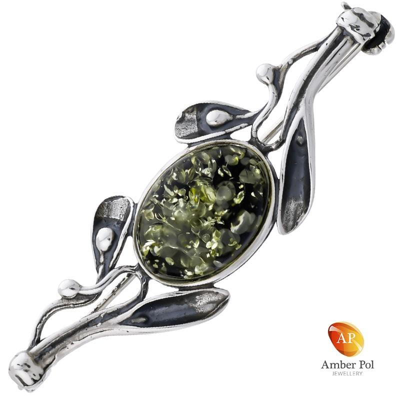 Broszka srebrna 925 z zielonym bursztynem otoczonym srebrnymi zdobieniami.