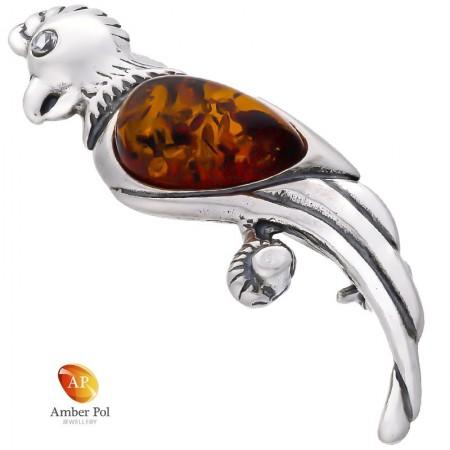 Broszka srebrna 925 o kształcie papugi z bursztynem w kolorze koniaku umieszczonym w skrzydełku jak i cyrkonii jako oczko.