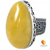 Pierścionek z dużym żółtym bursztynem w dekorowanej srebrnej oprawie.