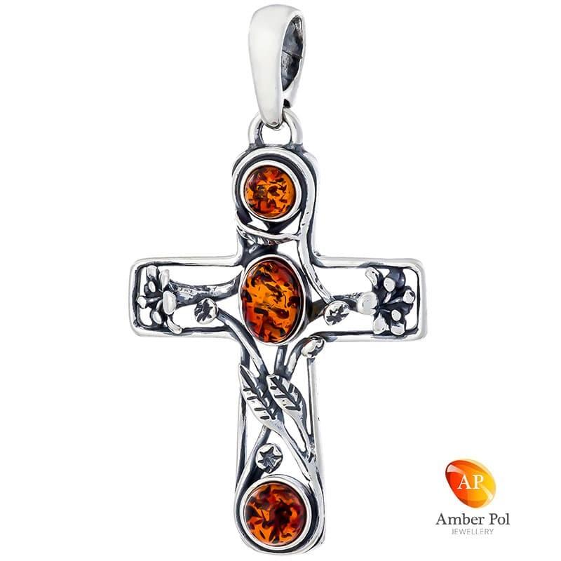Wisiorek ze srebra 925 z trzema bursztynkami wplecionymi w ramkę o kształcie krzyża, w środku również gałązki, kwiatki i listki.