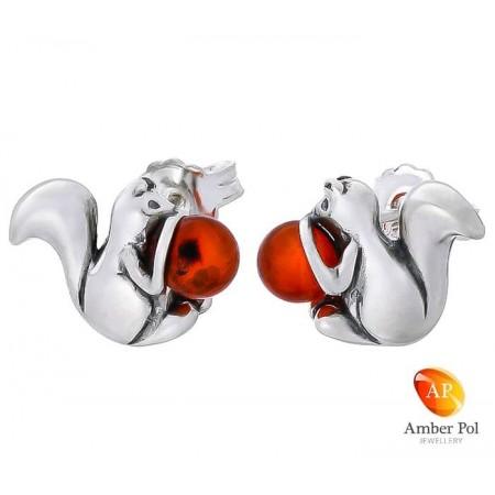 Kolczyki srebrne  na sztyft o kształcie wiewiórki obejmującą bursztynowa kulkę w koniakowym kolorze.