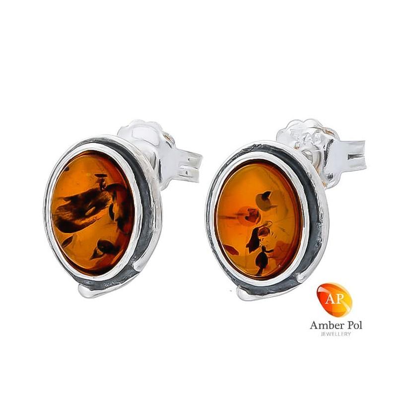 Piękne kolczyki na sztyft ze srebra próby 925 o kształcie owalu z bursztynem w koniakowym kolorze.