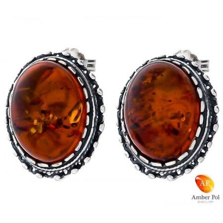 Piękne kolczyki na sztyft ze srebra próby 925 o kształcie owalu, zakute ręcznie z bursztynem w koniakowym kolorze.
