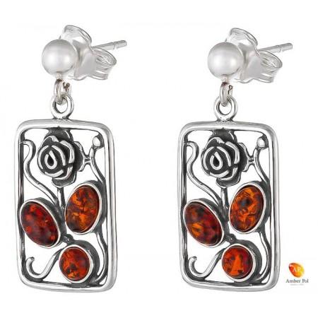 Kolczyki wiszące ze srebra 925 o kształcie ramki z różą na zawieszce typu bigiel zapinany i z trzema koniakowymi bursztynami.