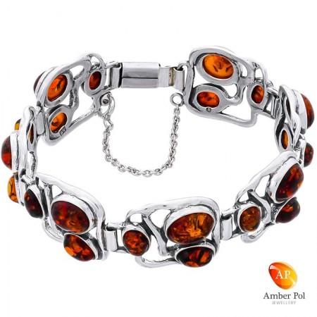 Srebrna 925 bransoletka z bursztynem koniakowym. posiada 7 elementów a w każdym po 3 owalne bursztyny w rożnej wielkości.