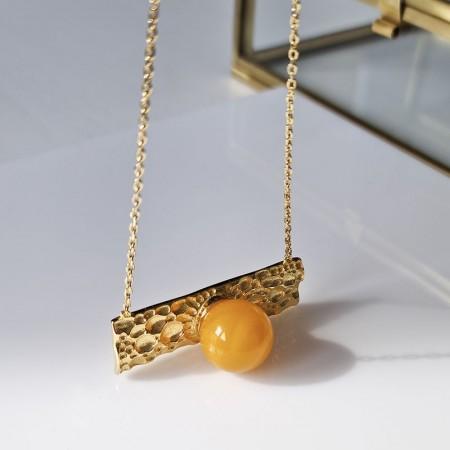 Naszyjnik ze srebra 925 pozłocony 24 karatowym złotem  ozdobnym panelem i bursztynową kulką w mlecznym kolorze.