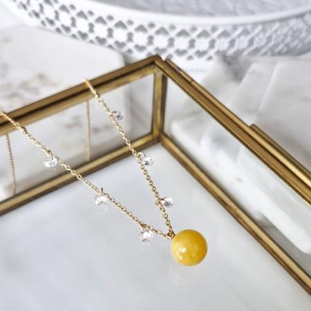 Naszyjnik ze srebra 925 pozłocony 24 karatowym złotem. Ozdobiony cyrkoniami i naturalnym bursztynem w białej barwie.