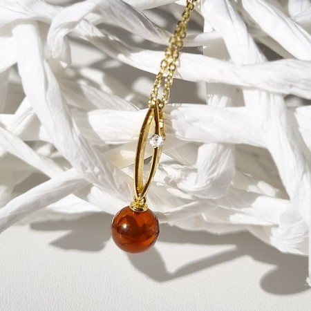 Naszyjnik srebrny pozłacany 24-karatowym złotem z wiśniowym bursztynem w kształcie kuleczki stworzony przez Amber Pol w Sopocie