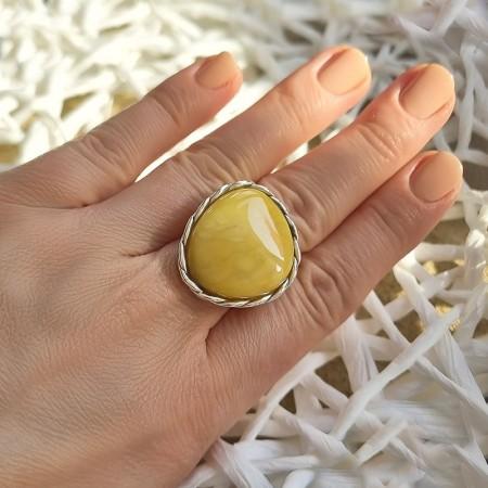 Unikatowy pierścionek ze srebra 925 z dużym bursztynem w żółtym kolorze ozdobionym plecioną oprawą.